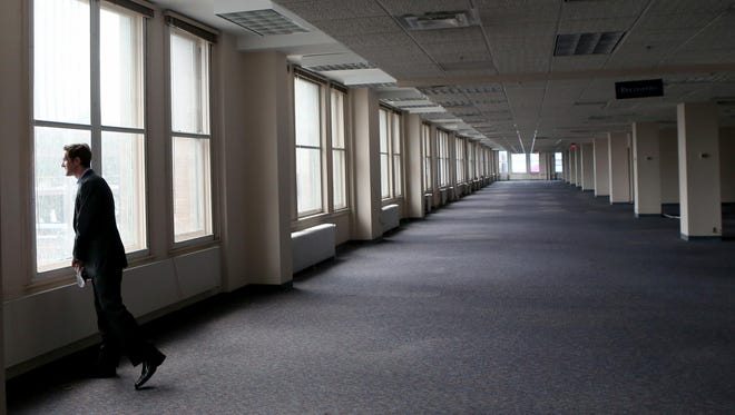 Joseph Eddy, vice president of WinnDevelopment, looks onto Main Street from the third floor window of the Sibley Building in Rochester. Sibley is being discussed as one potential site for the American Institute of Manufacturing (AIM) Photonics headquarters.