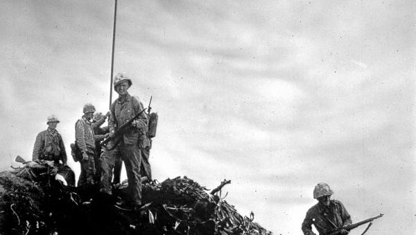 Photograph taken by Louis Lowery of the first flag raising on Iwo Jima, February 23, 1945. Platoon Sergeant Thomas stands on the mound with his rifle and faces the camera. Corporal Charles W. Lindberg, Navy Pharmacist's Mate 2nd Class John Bradley, Sergeant Henry Hansen, 1st Lieutenant Harold G. Schrier and Private Philip L. Ward are also in the photograph.
