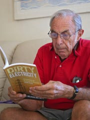 """Samuel Milham looks through his book, """"Dirty Electricity: Electrification and the Diseases of Civilization,"""" during an interview with The Desert Sun at his Indio home."""