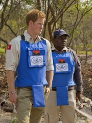 On Saturday, Aug. 17, 2013, Prince Harry, left, is given a tour around the mine clearance site in Angola.