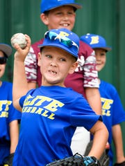 Seth Boggess, 7 years-old, winds up his fastball during pitching practice at the Henderson Flash's baseball camp for ages 8-15 held at B.T. Wayne field Monday, June 11, 2018.