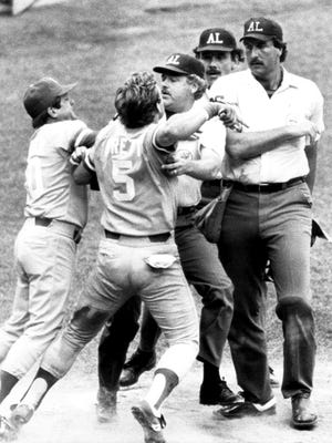 George Brett is restrained by umpire Joe Brinkman and manager Dick Howser as he tries to get to home plate umpire Tim McClelland.