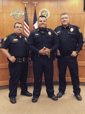 Robstown Police Officer Jimmie Zamora, center, stands with Lt. Albert Stout, left, and Chief Erasmo Flores, right, after Zamora received an award for saving an infant's life in June 2018.