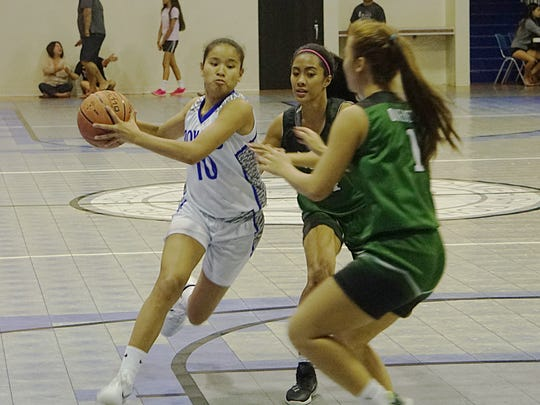 Notre Dame Royals senior Destiny Castro drives past, from left, Regine Tugade and Anita Onedera on her way to 25 points in the Royals' 74-32 home win against the John F. Kennedy Islanders on Friday, Dec. 11.