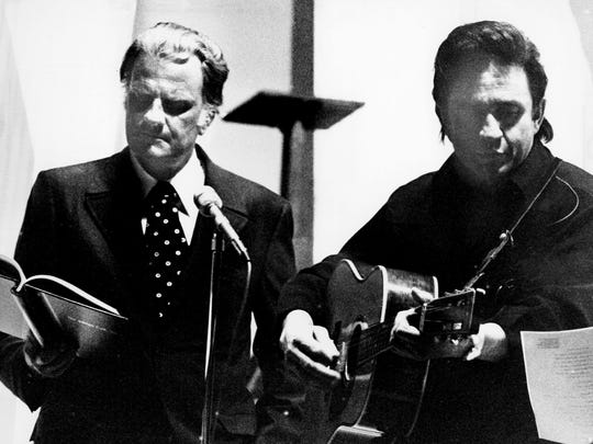 Evangelist Billy Graham, left, reads his Bible while Johnny Cash plucks his guitar before the Ryman Auditorium audience Jan. 31, 1971. The evangelist joined his old friend for a taping of the country star's Feb. 28 network TV show devoted solely to gospel music. Graham confessed to a bit of nervousness.