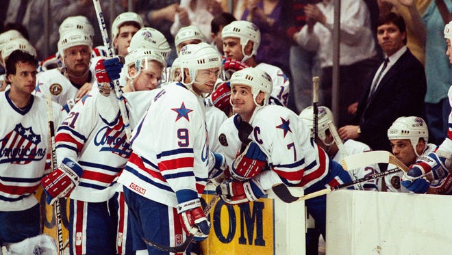 Jody Gage celebrates with Steve Ludzik (7) and other teammates after breaking Dick Gamble's scoring record in 1992.