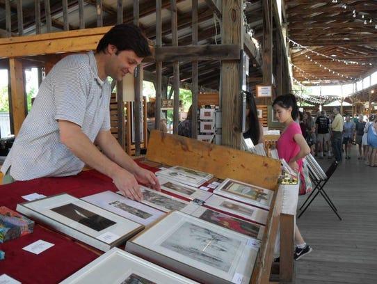 Michael Sampson sets up artwork at a previous Ithaca