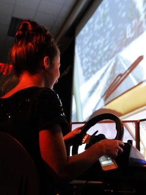 Two Rivers High School senior Carly Terp texts while driving in the AAA's distracted driving simulator.