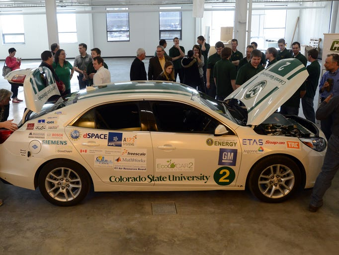 A crowd gathers around the Chevy Malibu EcoCAR 2, entry, at the CSU Powerhouse Energy Campus Thursday March 13, 2014.  Colorado State Universityâ??s Vehicle Innovation Team has re-engineered a 2013 Chevrolet Malibu that emits only water as part of the national EcoCAR 2 competition. The CSU vehicle operates on a combination of compressed hydrogen gas and electricity, and uses no gasoline. Its only emission is clean water produced by a reaction between fuel cells, hydrogen, oxygen and electricity for propulsion. With the combination of hydrogen gas and electricity, consumers can either charge their vehicle at home or work for short daily commutes (50 or fewer miles) or fill up on hydrogen for trips of 200-plus miles.
