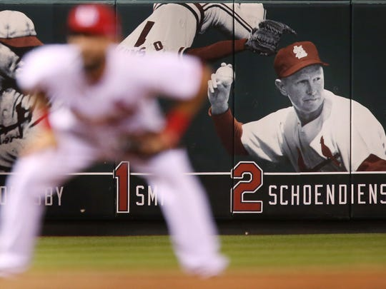 An image of Red Schoendienst and his uniform No. 2 are on the wall of retired numbers in left field at Busch Stadium in St. Louis on Wednesday, June 6, 2018. The St. Louis Cardinals announced the death of Schoendienst on Wednesday. In the foreground is Cardinals third baseman Matt Carpenter, during the team's game against the Miami Marlins. (Chris Lee/St. Louis Post-Dispatch via AP)