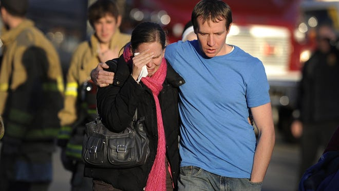Alissa Parker and her husband, Robbie Parker, leave the firehouse staging area after receiving word that their 6-year-old daughter, Emilie, was one of the 20 children killed in the Sandy Hook Elementary School shooting in Newtown, Conn., on Dec. 14, 2012.
