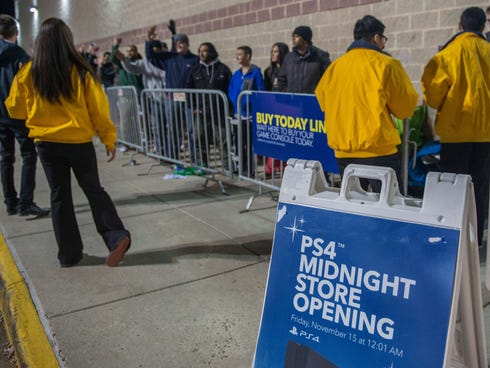 Customer service representatives in yellow brief camped-out shoppers as they wait in line to purchase the new PlayStation 4 at a midnight opening at Best Buy in Fairfax, Va.
