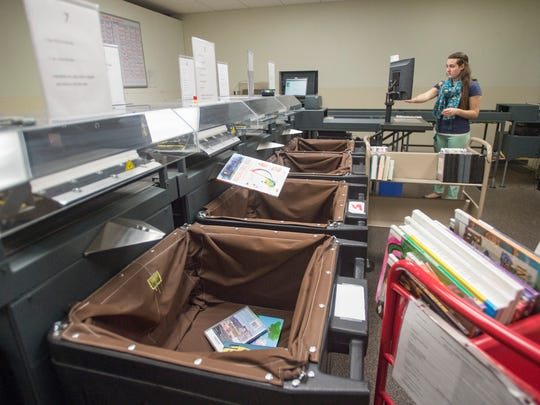 Circulation Specialist Kindra Baker uses a sorting belt to process incoming materials at Old Town Library on Thursday, April 26, 2018. The device is capable of sorting thousands of books, movies and other library stock each day.