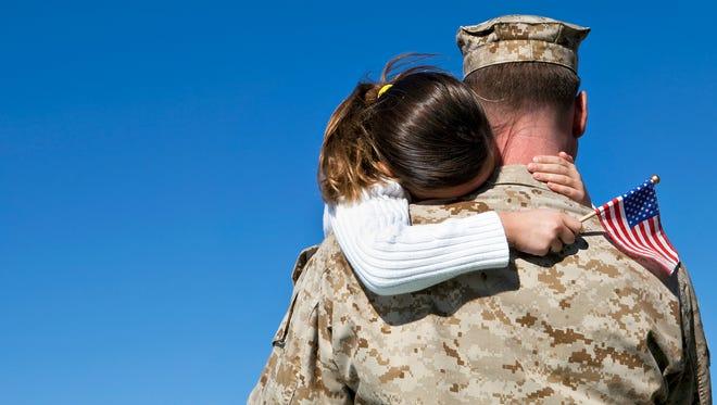 A serviceman hugs his child.
