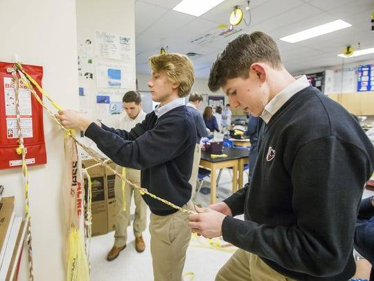 Newark Charter National Honor Society students braid plastic bags that will woven into sleeping mats.