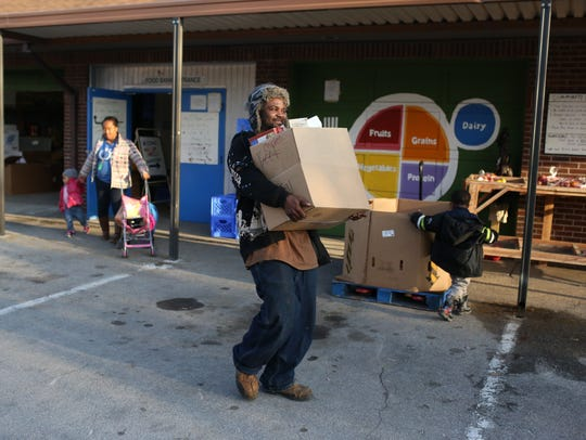 Clyde Edwin Jr. carries boxes of food for his family