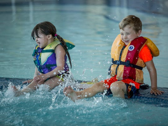 Carter Newman, of Clyde Township, and Addy Fleming, of Port Huron, both 4, kick their feet during a beginning swim class Thursday, June 23, 2016 at the YMCA of the Blue Water Area.