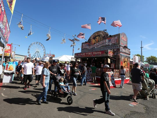 Fairgoers browse the booths on the final day of the