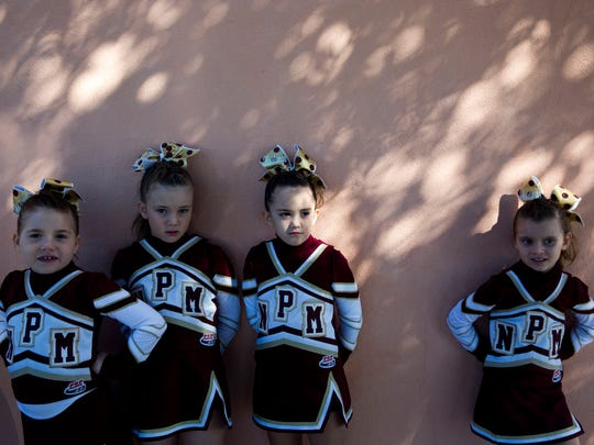 Girls with the North Port Mustangs wait to be called into Germain Arena during the 2016 Peace River Conference Pop Warner Cheerleading Competition Sunday, Oct. 23, 2016, in Estero, Fla.