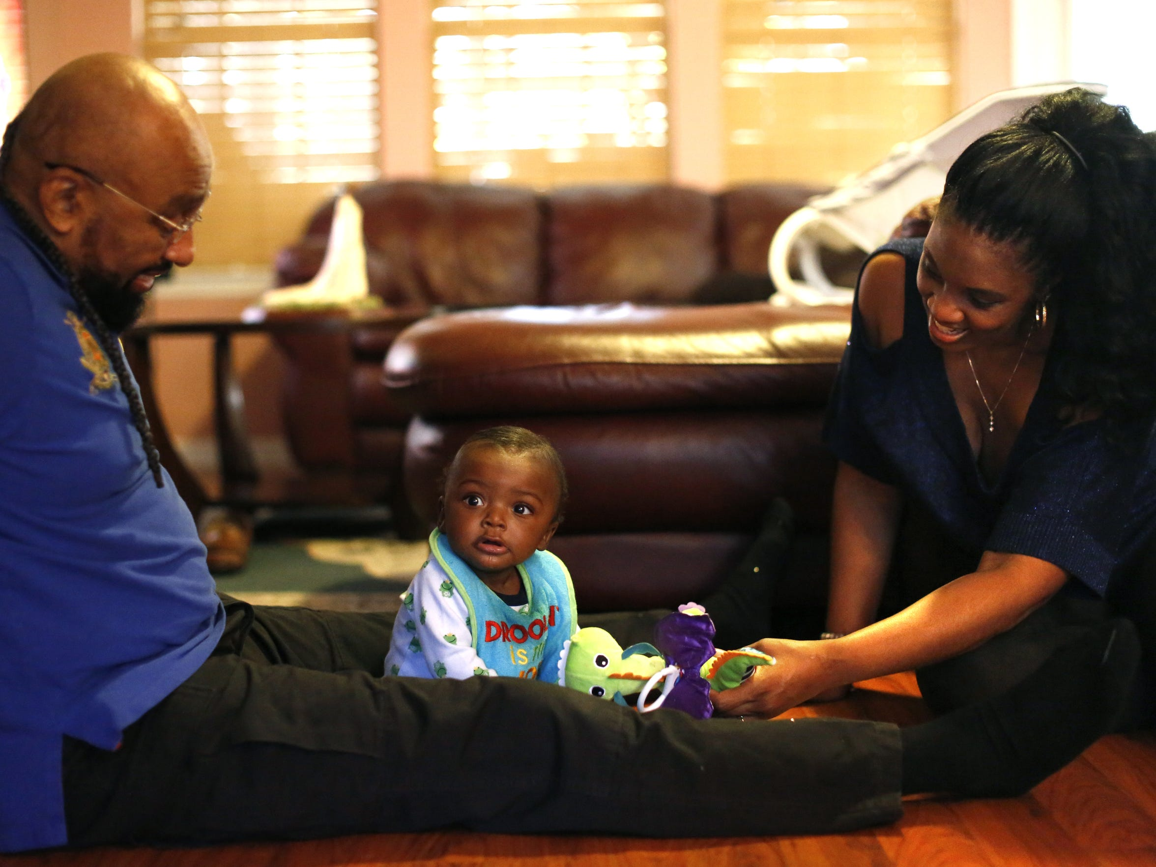 Charles and Lorraine Nichols play with their son Caleb Charlie Nichols, seven mo., in their living room Dec 12. Lorraine first laid eyes on the baby when she cared for him at TMH where he was brought after being discovered in the back of a pickup truck. Four days later she took him home to join her family.