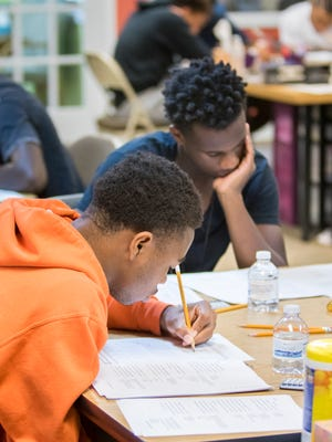 Deterius Gideon, of Catholic High School, left, fills in an answer as he and other student-athletes participating in the Mr. Robbins Neighborhood program take a practice ACT test at Sylvan Learning Center in Pensacola on Saturday, October 14, 2017.