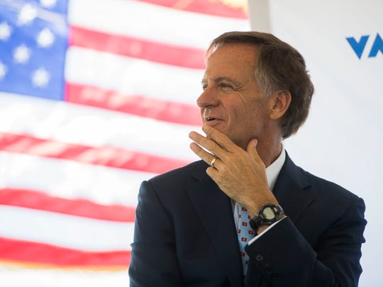 Gov. Bill Haslam smiles as the American flag waves behind him during the announcement of Belgian bus company Van Hool building a factory in Morristown, Tenn. and creating more than 600 jobs, Thursday, April 12, 2018.