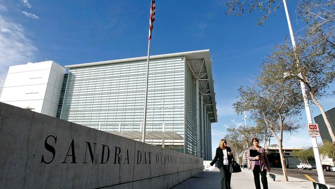 Pedestrians walk past the Sandra Day O'Connor United States District Court where a federal civil rights trial against two polygamous towns on the Arizona-Utah border began, Tuesday, Jan. 19, 2016, in Phoenix.