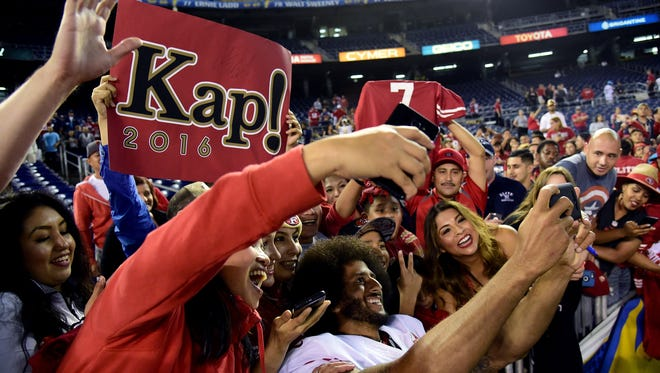 Colin Kaepernick #7 of the San Francisco 49ers poses for photos with fans after a 31-21 win over the San Diego Chargers during a preseason game at Qualcomm Stadium on September 1, 2016 in San Diego, California.