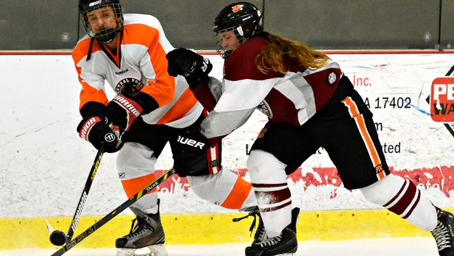 Central York's Gavin Lyter, left, and Manheim Central's Madalyn Nelson work against each other to control the puck during ice hockey action at York City Ice Arena in York City, Monday, Dec. 5, 2016. Central will play in the Central Penn Interscholastic Hockey League Rothrock Division this season. Dawn J. Sagert photo
