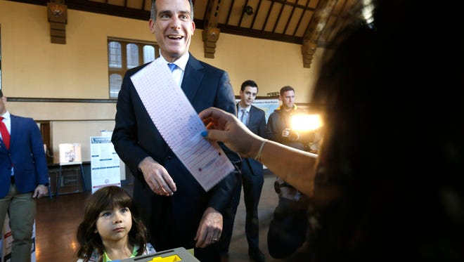 Los Angeles Mayor Eric Garcetti casts his election ballot with his daughter Maya in Los Angeles, on Tuesday.