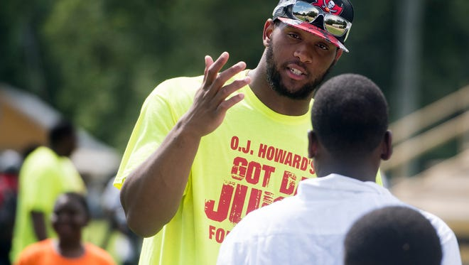 O J Howard talks with students at an event where he gives out backpacks to children at the Autauga Academy campus in Prattville, Ala. on Sunday July 9, 2017.