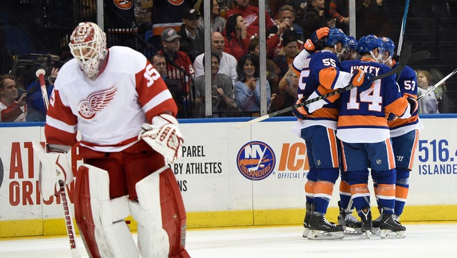 The Islanders celebrate Cal Clutterbuck's goal as Red Wings goalie Jimmy Howard skates away in the second period.