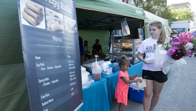 Kyra Robinson, left, helps carry egg rolls with Jessica Jorgenson on Saturday, Sept. 23, 2017, during the Oshkosh Saturday Farmers Market.