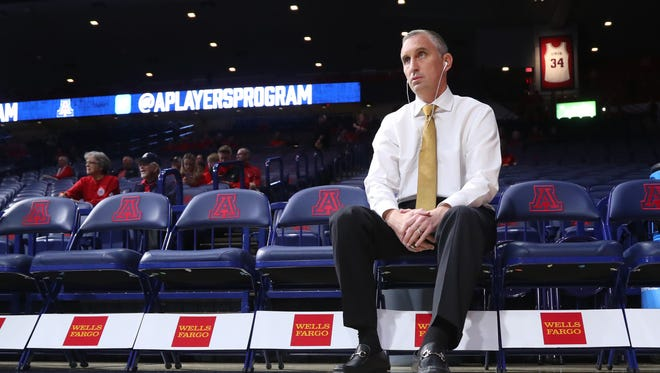 ASU's head coach Bobby Hurley sits listening to headphones before a game against Arizona on December 30, 2017 in Tucson, Ariz.