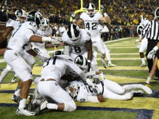 Michigan State defensive back Jalen Watts-Jackson (20) is surrounded by jubilant teammates after he recovered a fumbled snap on a punt in the closing seconds of the second half and returned it for a touchdown during an NCAA college football game against Michigan, Saturday, Oct. 17, 2015, in Ann Arbor, Mich. Watts-Jackson lumbered 38 yards for a touchdown on the final play of the game, giving No. 7 Michigan State a shocking 27-23 win over No. 12 Michigan. (Melanie Maxwell/The Ann Arbor News/MLive.com via AP)