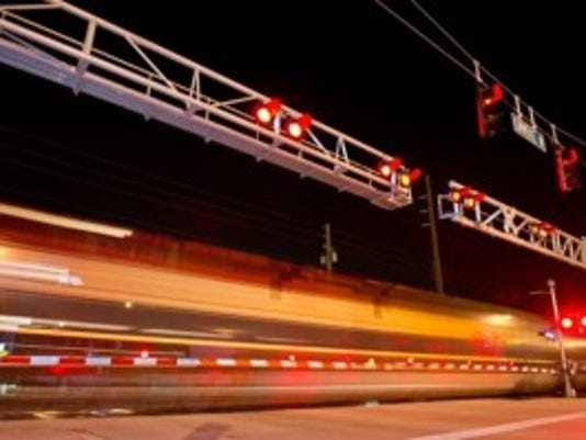 XAVIER MASCAREÑAS/TREASURE COAST NEWSPAPERS - A freight train rolls past the 20th Place and Commerce Avenue crossing for the Florida East Coast Railway tracks in downtown Vero Beach on June 25.