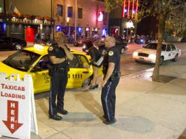 Des Moines Police Sr. Officers Luke Wilson, left, and Brady Carney help part goers hail cabs as they work the Taxicab line on 3rd Street in the Court Avenue entertainment district.