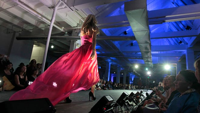 Models walk the runway in 2014 Fashion Week of Rochester. This week's event is located in one space: a tent in downtown Rochester.