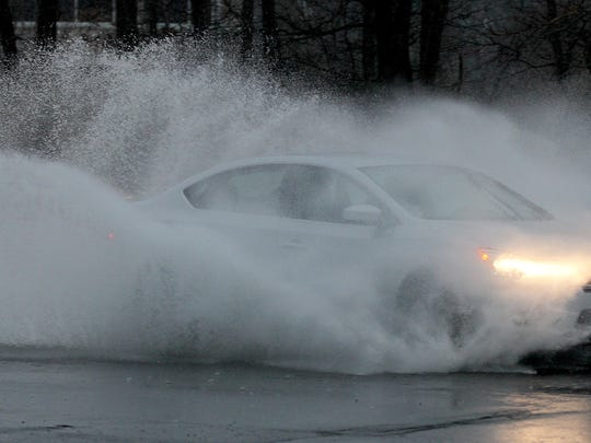 A car drives through standing water on Route 34 in Wall Township Tuesday, March 14, 2017.