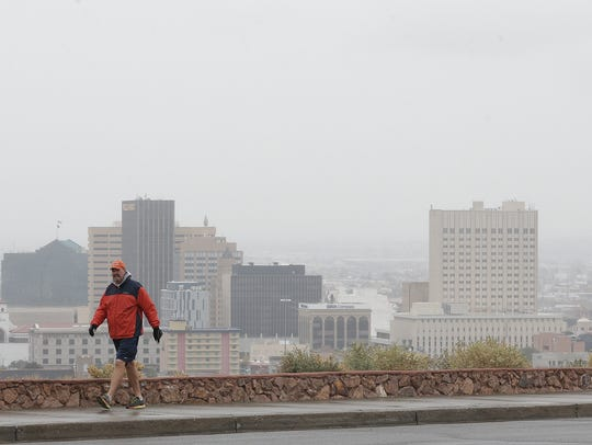 A man walks along Rim Road despite rainy, cold conditions