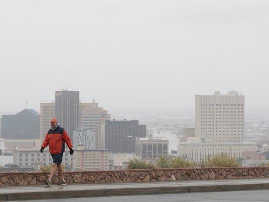 A man walks along Rim Road despite rainy, cold conditions in December in El Paso.