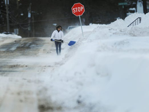 A resident shovels snow as a gust of wind whips around