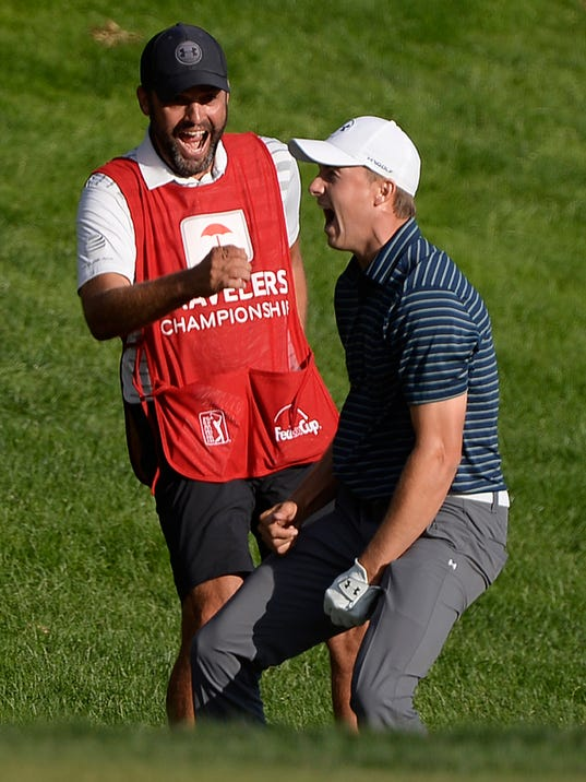 FILE - In this Sunday, June 25, 2017, file photo, Jordan Spieth celebrates with caddy Michael Greller after sinking a shot from a bunker on the first playoff hole for the win during the final round of the Travelers Championship golf tournament, in Cromwell, Conn.  In his first year as PGA Tour commissioner, Jay Monahan said his top priority was to make Arnold Palmer proud. Monahan says moments like Spieth's victory are things that remind him of Arnold Palmer's appeal. (AP Photo/Jessica Hill, File)
