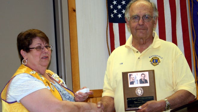 Thomas Stram of the Marshfield Lions Club receives a plaque on June 21 from Past President Lion Lily Michalski.
