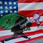 A banner shows a vulture, symbolizing a U.S. hedge fund, carrying a bag of money in front of the U.S. flag outside Congress in Buenos Aires, Argentina, Wednesday, Sept. 10, 2014.