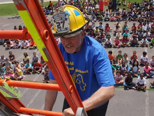 MacAfee Road School students watch as principal Bill Grippo climbs to the roof of the school where he will spend the night, Tuesday, June 17, 2014, in Franklin, NJ. Photo by Jason Towlen
