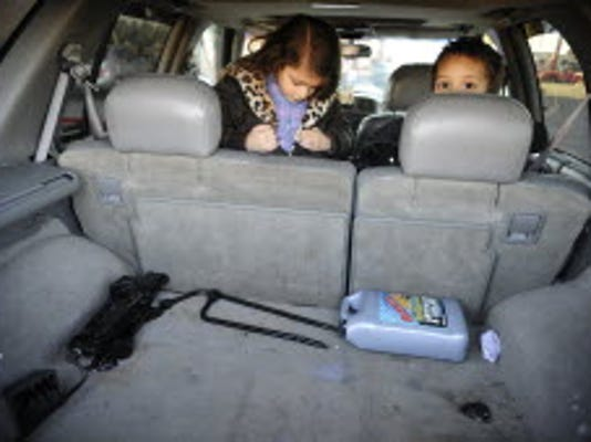 Duvall Hughes' children Tierra, 6, and Duvall, Jr., 3, peek over the back seat Friday at Hughes' fairly empty trunk. Hughes of Manchester Township said he typically keeps emergency supplies, including jumper cables in his vehicle, but aside from a tire iron, a tire jack and antifreeze, his trunk is largely empty because of a recent move. DAILY RECORD/SUNDAY NEWS - CHRIS DUNN