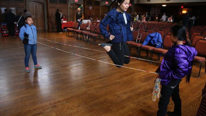 Paw Thaw Kya, 13, middle, plays Chinese jump-rope with Say Ku Wah, 11, left, and Eh Ser Ya, 11, at Asian Pacific American Heritage Family Day at the Memorial Art Gallery.