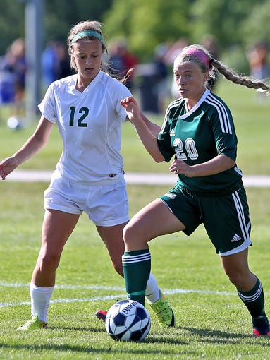 Iowa City West's #20 Emma Cooper, right, moved the ball down field as Dubuque Hemstead's #12 Holly Bitter, left, gave chase during Class 3-A quarterfinal match at the 2014 Girls' State Soccer Tournament at the Cownie Soccer Complex on Thursday June 12, 2014.