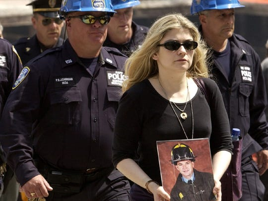 Christina Regenhard holds a portrait of brother Christian, a New York City firefighter lost in the Sept. 11 attack on the World Trade Center, as she is escorted by Port Authority police officers during a service at ground zero May 30, 2002, marking the end of more than eight months of cleanup and recovery efforts at the World Trade Center site in New York.